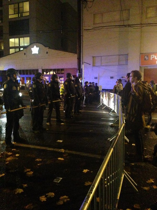 Seattle police have another blockade on 12th Ave. Different group of Ferguson protesters staring at them.