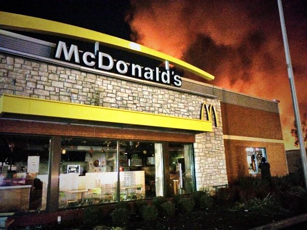McDonald's windows smashed as the light from a business burning shines behind in Ferguson: