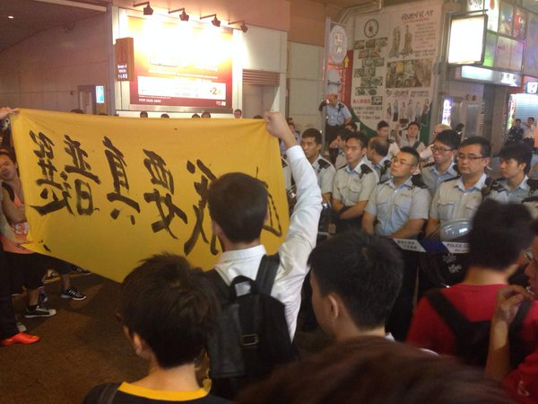 Students now parade the banner in front of police line. Crowd continue to chant the words. OccupyHK