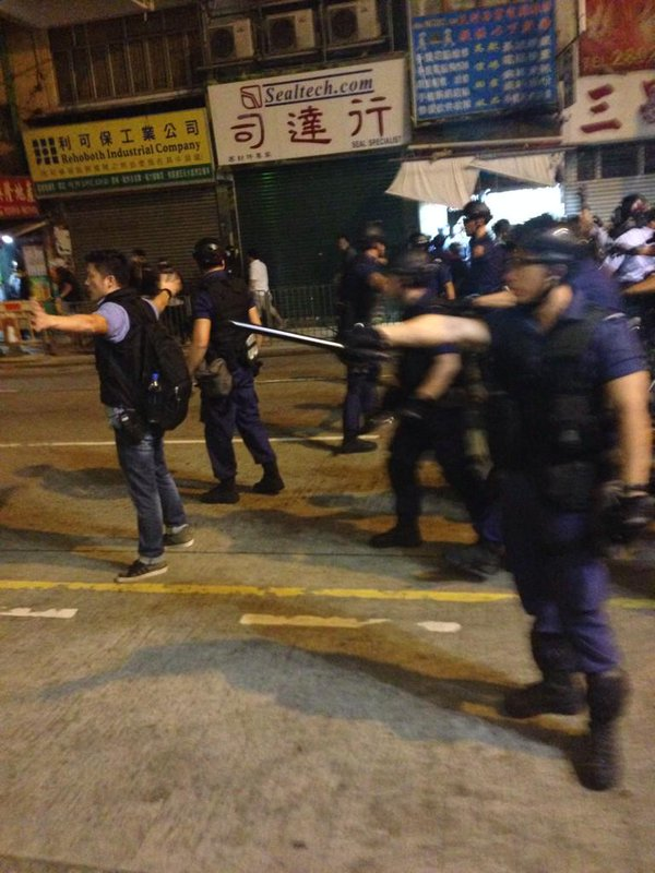 Police rush out and turn corner, pushing protesters onto reclamation street