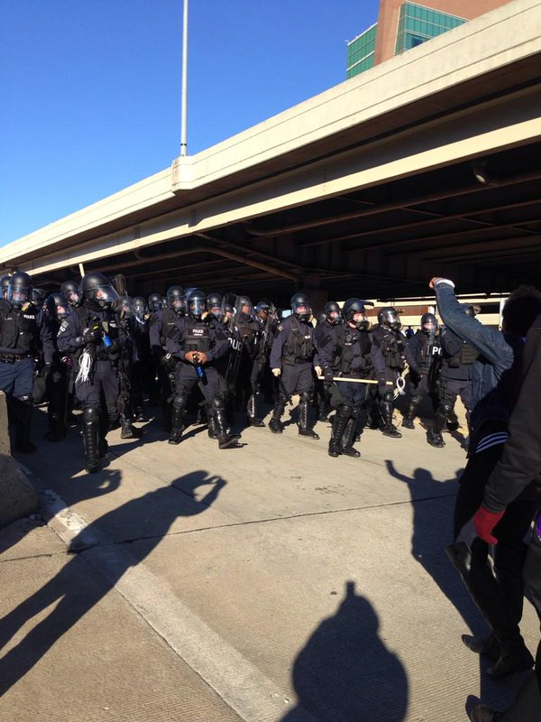Police in riot gear marching down the ramp behind remaining protesters, police banging.