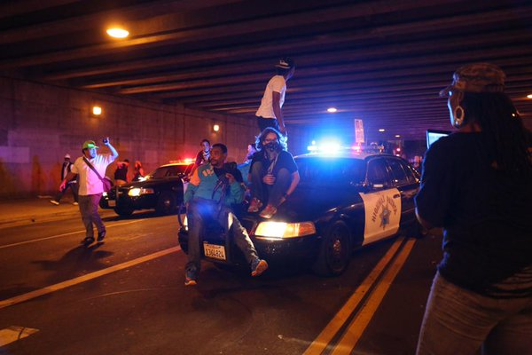 Protesters escalate confrontation as they surround LAPD and climb on cars