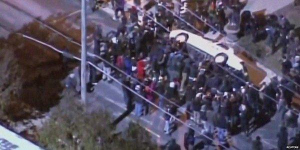 Ferguson protesters overturn police car.