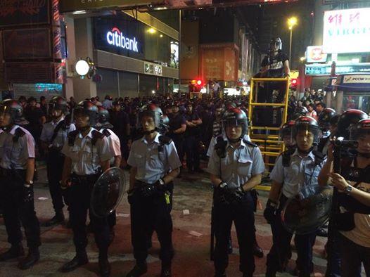Police wear helmets and shields.