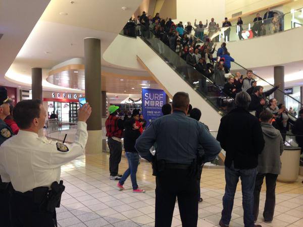 March continues through Chesterfield Mall as police and shoppers look on. Most stores close doors. Ferguson