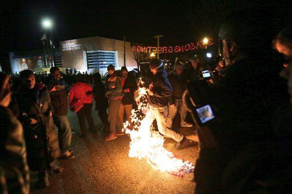 Ferguson protesters light an American flag on fire outside the police station
