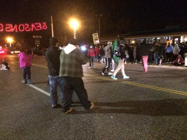 A dozen protesters in the road in front of Ferguson PD.