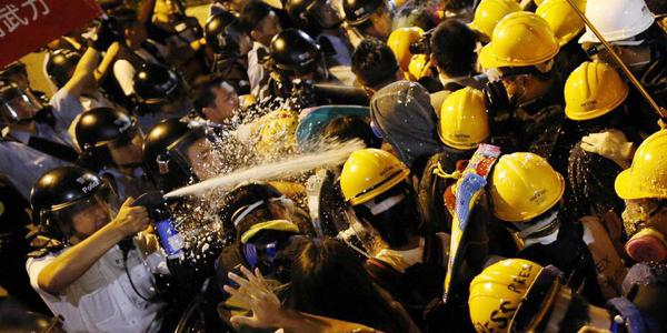 Police use pepper spray to disperse protesters in Hong Kong near the Financial District.