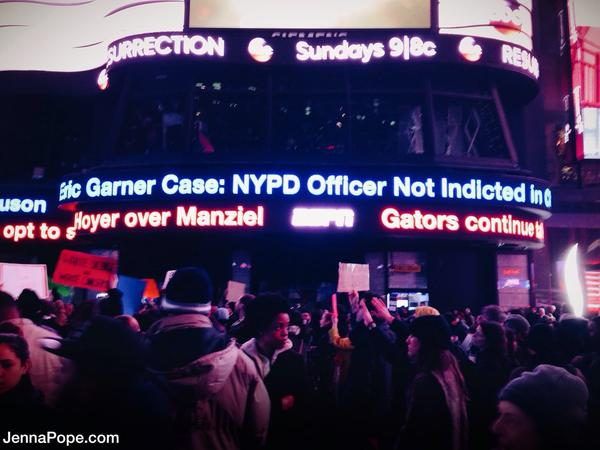 Hundreds of people rally in Times Square as EricGarner headlines flash in the background.