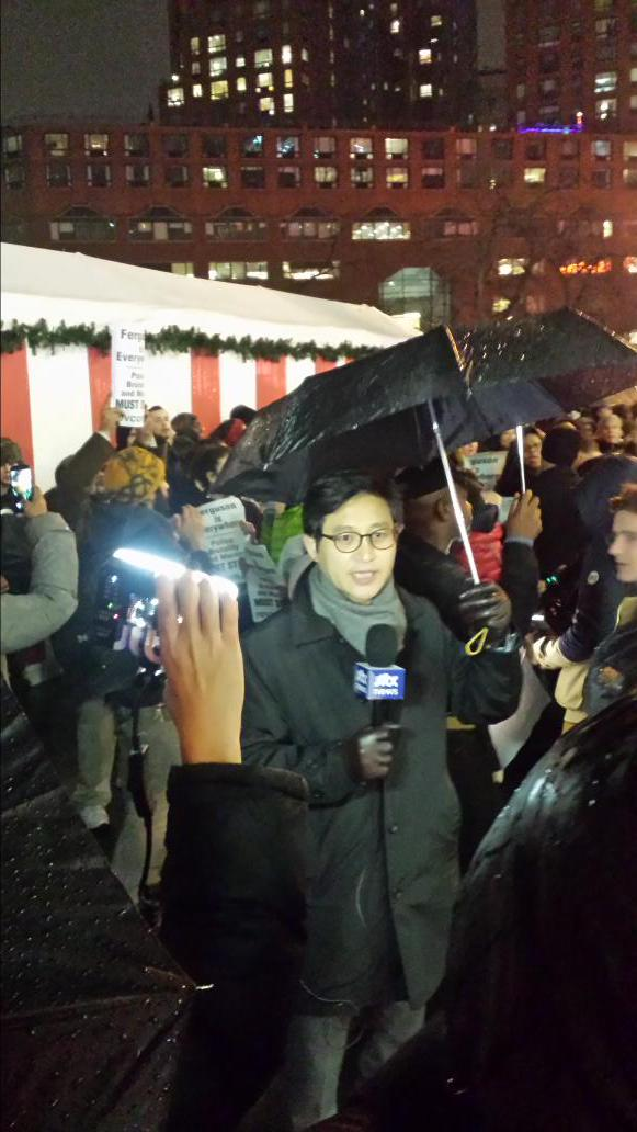 TV news from Japan doing piece to camera in rain in front of EricGarner protesters in Union Square NYC