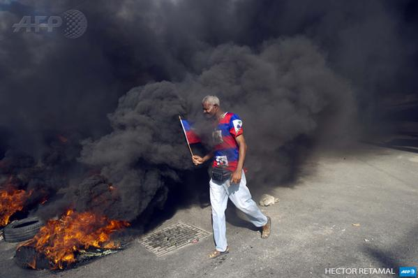 A protester passes a burning tire during a protest against the government in Port-au-Prince