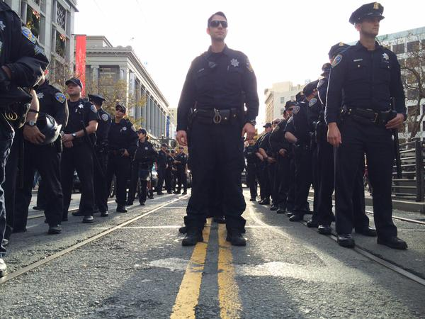 Police line up single file behind protest on Market street in SF