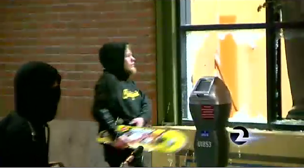 Protester smashes store window with skateboard during HandsUp protest Berkeley.