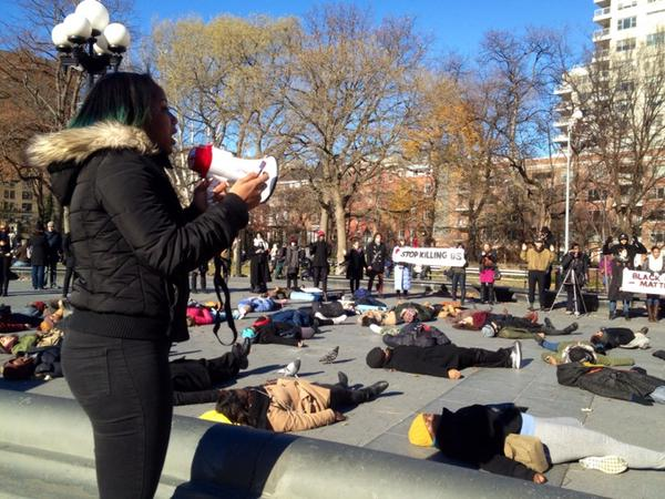Speaker reading off UN's def. of genocide at die in at Washington Sq park NYC