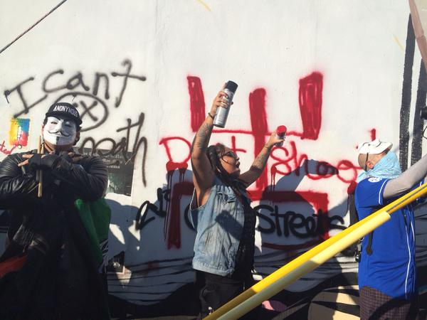 Some protesters spray paint I can't breathe and don't shoot on the wall. Miami