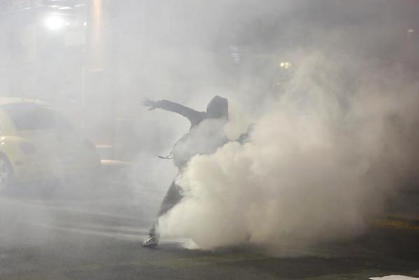 Protester in Northern Oakland hurls a tear gas canister back at California Highway Patrol