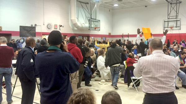 Chants begin. Chief Dotson drowned out. Backs turned. FergusonCommission