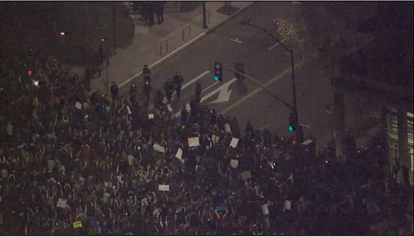 Riot police  just poured out of berkeley PD to reinforce skirmish line. Large crowd w/ hands up