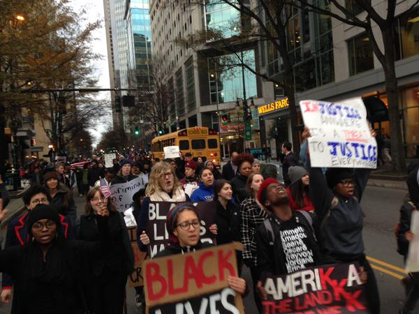 EricGarner protesters in Charlotte, NC marching down middle of Tryon St after shutting down Square