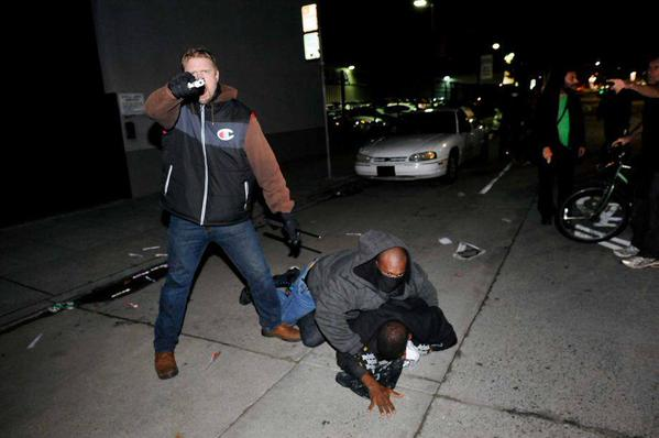 Here is an image of one of last nights undercovers pointing his gun directly at a person with a camera. oakland