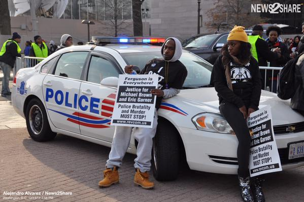Two protesters relax on a DC police car at the Justice4All rally against police brutality