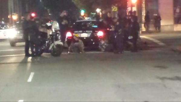 A couple women in handcuffs seated next to a cop car at 18th and Franklin. oaklandprotest