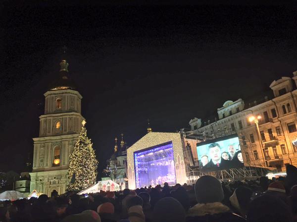 Poroshenko address nation. People at rally at Sofiivska watching